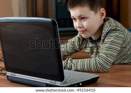 little boy lying down on the floor in the living room and playing computer game on laptop - stock photo