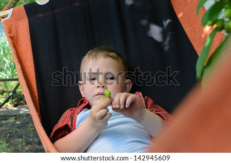 Little boy lying in a hammock in the shade of a tree looking at the camera - stock photo