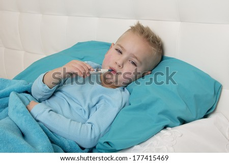 little boy lying in bed with a thermometer in his mouth - stock photo