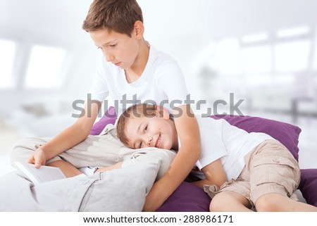 Little boy lying, listening a story. Older brother reading a book. Family photo.