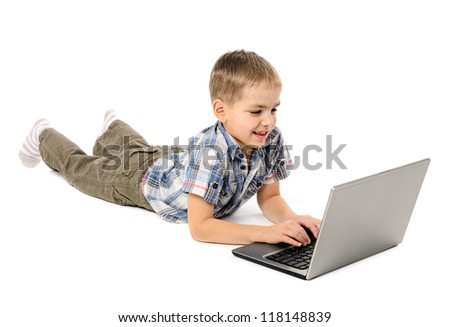 Little boy lying on a white background using a laptop - stock photo
