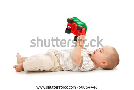 Little boy lying on back and playing with plastic toy car - stock photo