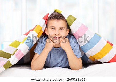 Little boy lying on bed covered with a blanket at home - stock photo