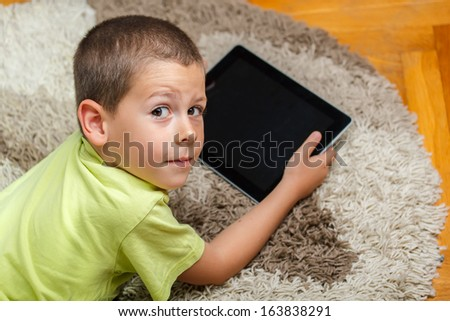 Little boy lying on floor and using digital tablet - stock photo