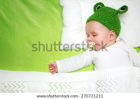 little boy lying on soft green blanket - stock photo