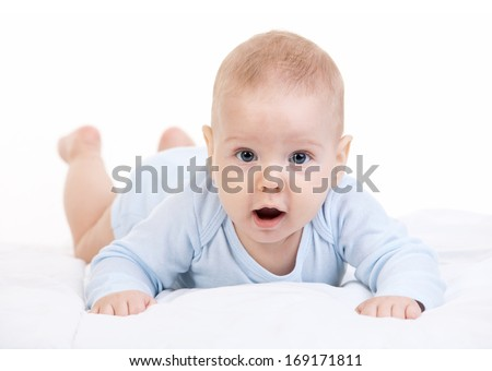 Little boy lying on stomach and looking at camera over white background  - stock photo