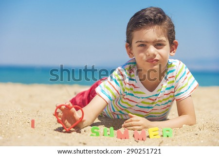 Little boy lying on the beach. Photographed with shallow depth of field. Image cross processed for vintage look. - stock photo