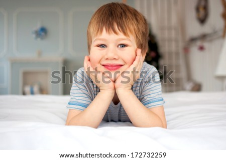 Little boy lying on the bed and smiling. Good morning! - stock photo