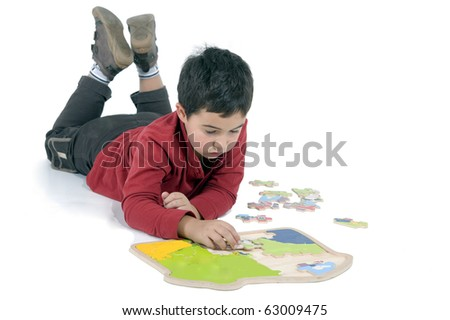 little boy lying on the floor making puzzles