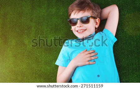 Little boy lying on the grass and dreaming. Beautiful boy in glasses looking at the camera. Sunny summer season. Baby pictures - stock photo