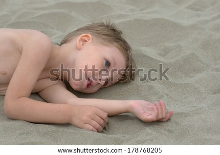 little boy lying on the sand - stock photo