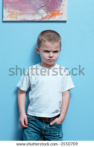 Little boy mad look on his face standing against a wall
