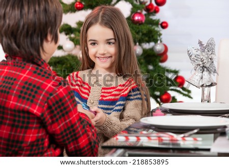 Little boy make a present to his sister for Christmas. Decorated table and tree on background. - stock photo