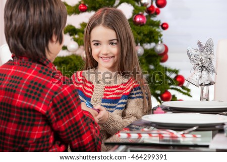 Little boy make a present to his sister for Christmas. Decorated table and tree on background.