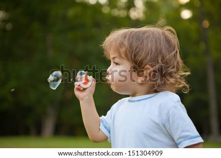 Little boy make a soap bubbles in park - stock photo