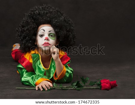 little boy, make-up of the clown with roses - stock photo