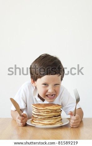 Little boy making evil face over a pile of pancakes - stock photo