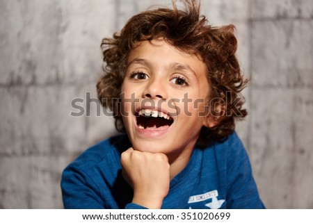 Little boy making faces while looking at camera - stock photo