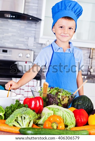 Little boy making salad in the modern kitchen. Wearing a cook's hat - stock photo
