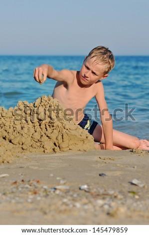 Little boy making sand castle at beach - stock photo