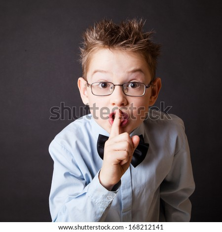 Little boy making sign with his finger to keep silence