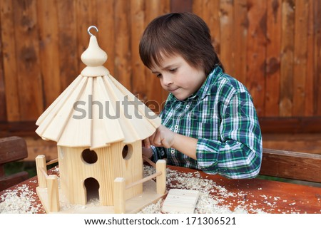 Little boy making the last finishing touches on a wooden bird house he is building - stock photo