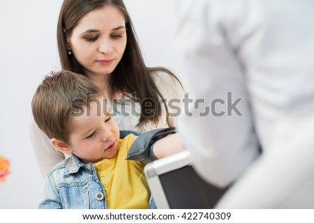 Little boy medical visit - doctor measuring blood pressure of a child - stock photo