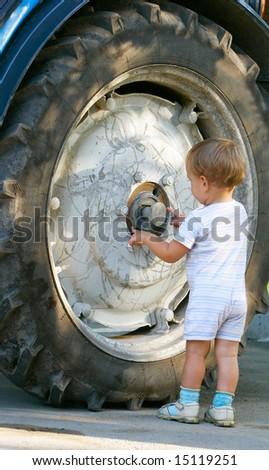 little boy near big truck wheel - stock photo