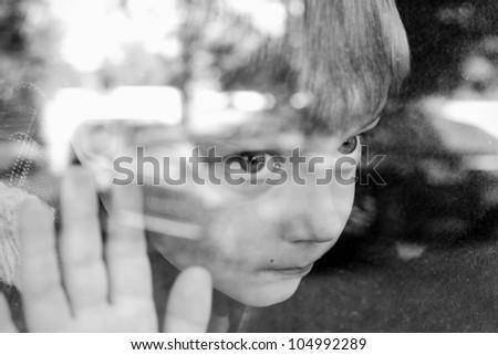 Little boy near window sad,brown toning,old style,shallow DOF - stock photo