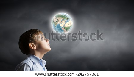 Little boy of school age looking at Earth planet. Elements of this image are furnished by NASA