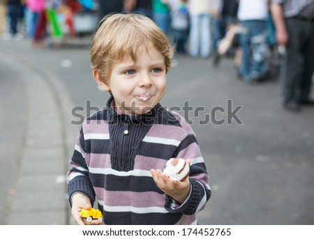 Little boy of three years eating sweets at a funfair, outdoors.