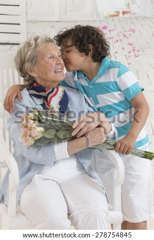 Little boy offering a bouquet of flowers to his grandmother - stock photo