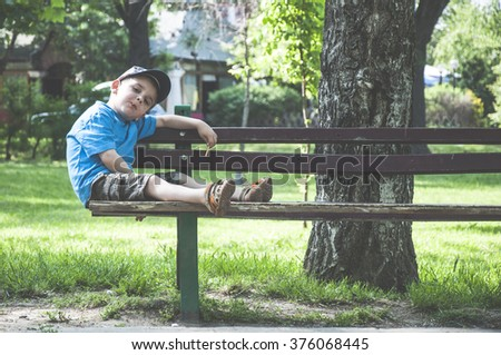 Little boy on a bench in the park.