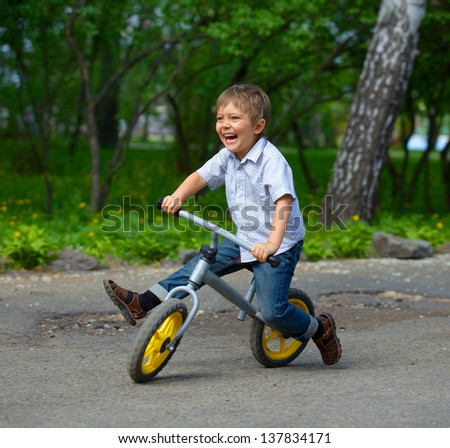 Little boy on a bicycle and his mother in the summer park - stock photo