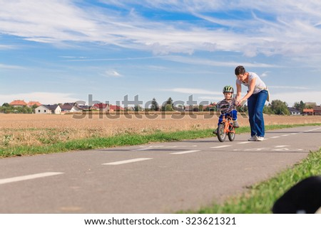 Little boy on a bicycle for the first time. - stock photo