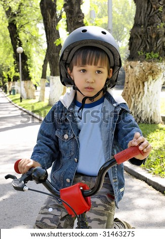 Little boy on a bike in a helmet.