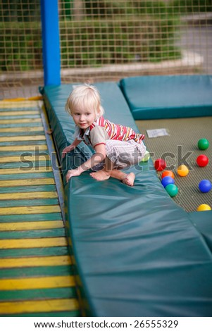 Little boy on a children's playground on a trampoline - stock photo