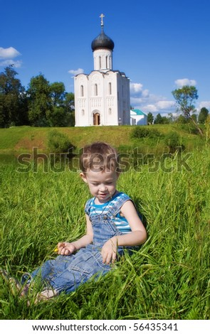 Little boy on a  orthodox church background. Church of the Intercession on the Nerl, Vladimir region of Russia - stock photo