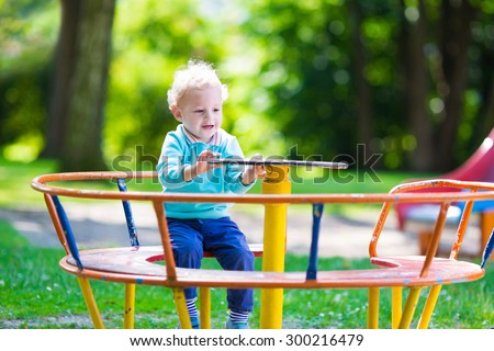 Little boy on a playground. Child playing outdoors in summer. Kids play on school yard. Happy kid in kindergarten or preschool. Children having fun at daycare play ground. Toddler on a swing. - stock photo