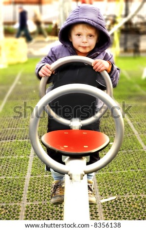 Little boy on a see-saw in the playground. - stock photo
