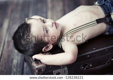 Little boy on a suitcase - stock photo
