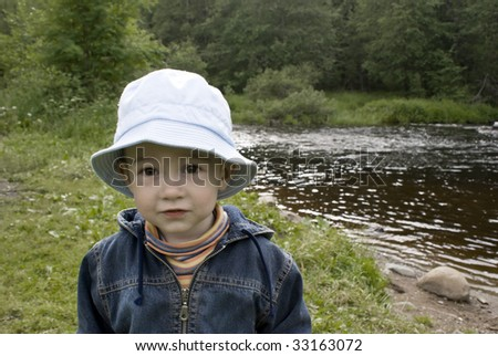 Little boy on a summer wood and river background - stock photo
