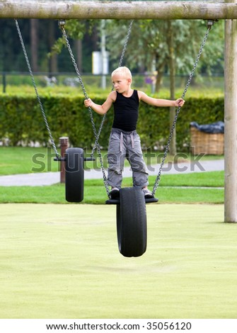 Little boy on a swing chair of a tire - stock photo