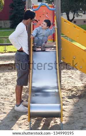 Little boy on a top of slide in an outdoor playground with a father helping and securing the child. - stock photo
