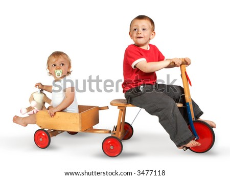 Little boy on a tricycle with his sister in a little cart - stock photo