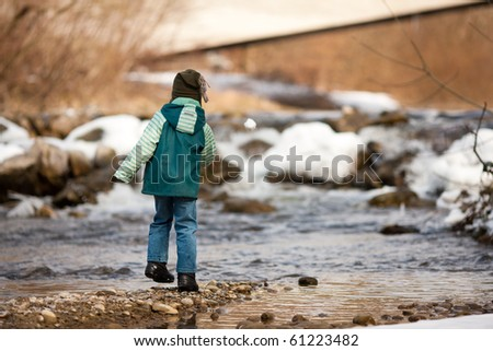 Little boy on a walk along a riverbank in winter; the child is throwing a snowball - stock photo