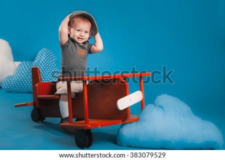 Little boy on a wooden plane - stock photo