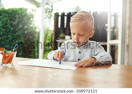 Little boy on an outdoor patio sitting at a wooden table drawing with colored crayons on sheets of white paper as he amuses himself during the summer vacation