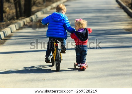 little boy on bike teaching baby girl to ride scooter outdoors - stock photo