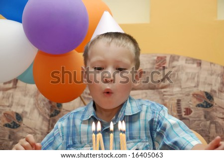 Little boy on birthday party blowing 6 lights - stock photo